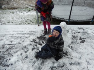 20150713 snow day 1 - snowman, Archie eating snowman's nose
