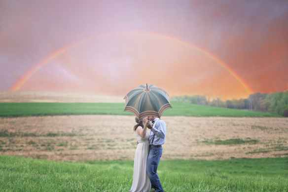 photo of couple holding umbrella while kissing